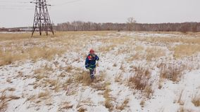 Electrician man going on the snow field at electrical station. With electric tower at background. Drone view: lineman finish electricity repair of voltage wires stock video