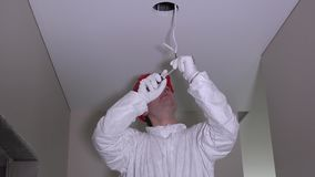 Electrician man making electricity installation on ceiling in new building stock footage