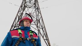 Electrician man standing on the power line and open helmet stock video footage
