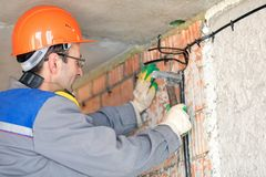 Electrician man worker installing electrical cable at house wall. Electrician man construction worker installing fuse box electrical cable at house wall royalty free stock photo