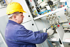 Electrician measure voltage. One electrician builder at work with tester measuring high voltage of power electric line in electical distribution fuseboard Royalty Free Stock Photo