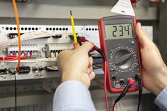 Electrician measurements with multimeter tester. Male Technician Examining Fusebox With Multimeter Probe stock photos