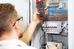 Multimeter is in hands of electrician on background of electrical automation cabinet. An electrician is checking the voltage in an stock photography