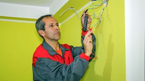Electrician Measuring With a Digital Multimeter. Electrician installs wiring in new apartment. Wiring an Outlet to an Electrical Box stock photo