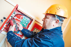 Electrician measuring electric circuit with multimeter in fuse box Stock Images
