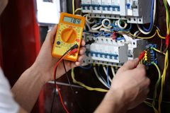 Electrician measuring voltage in distribution board. Closeup stock photos