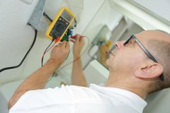 Electrician measuring voltage socket in new building closeup Stock Photo
