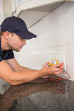 Electrician metering voltage with digital multimeter Royalty Free Stock Photography