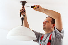 Electrician mounting ceiling lamp stock photos