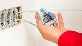 Electrician Mounting Electrical Wall Outlet. Male hand mounting new electrical outlet on tiled wall Stock Photos