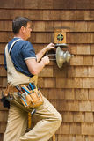 Electrician outdoor light. Professional electrician wearing tools installing outdoor patio light fixture Royalty Free Stock Image