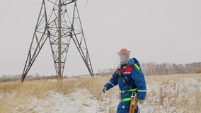 Electrician in overalls and helmet going repair the voltage wires. Professional electrician in overalls and helmet hurry going repair the voltage wires on the stock video