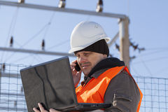 Electrician with PC and cell phone. Near the electricity substation Royalty Free Stock Images