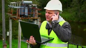 Electrician with PC talking on a cell phone stock footage