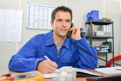 Electrician on phone in office. Electrician on the phone in his office stock images