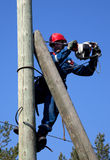 Electrician on a pole makes installation work Stock Images