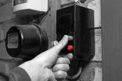 Electrician Pushing Red Knob. Electrician hand pushing red knob on a fuse box, selective color closeup shot Stock Photo