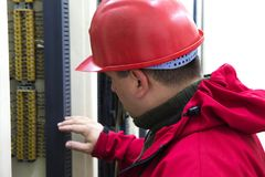 Electrician with red helmet control wiring in power plant stock photography