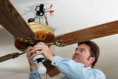 Electrician Removes Ceiling Fan. An electrician removing an old ceiling fan. The fan was installed without a ceiling box, in violation of code. Work is being Stock Images