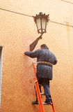 Electrician repairing a decorative streetlamp Royalty Free Stock Photo