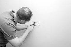 Electrician repairing electrical socket on white wall Stock Photo