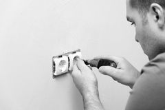 Electrician repairing electrical socket on white wall Stock Photography