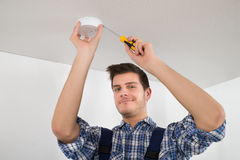 Electrician Repairing Fire Sensor. Male Electrician With Screwdriver Repairing Fire Sensor royalty free stock photo