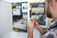 Electrician repairing fuse box with screwdriver indoors. Closeup stock images