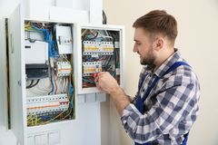 Electrician repairing fuse box with screwdriver. Indoors royalty free stock image