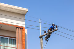 Electrician repairing wire on electric power pole. Royalty Free Stock Photography