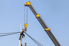 Electrician repairing wire of the power line on electric power pole with crane. Royalty Free Stock Image