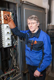 Electrician repairman in blue uniform standing near high voltage industrial panel Stock Photography