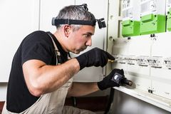Electrician repairs and measures fuse box or switch box royalty free stock photography