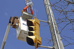 Electrician repairs traffic light overhead Royalty Free Stock Photo