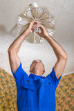 Electrician. The electrician replaces a bulb in a chandelier Royalty Free Stock Images