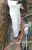 Electrician in road excavation during the repair job of a large Stock Images