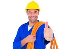Electrician with rolled wire gesturing thumbs up. Portrait of happy electrician with rolled wire gesturing thumbs up on white background Royalty Free Stock Photo