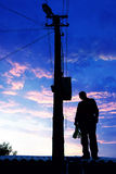 Electrician on the roof. Looking around before repairs power line Royalty Free Stock Images