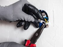 The electrician`s hands connect the wires in the socket using pliers. And special connectors Royalty Free Stock Image