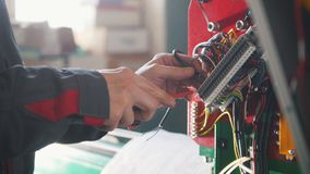 Electrician`s hands installing energy system on machinery industry. Close up Stock Image