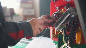 Electrician`s hands installing energy system on machinery industry. Close up stock photography