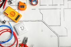 Electrician`s tools and space for text on house plan. Flat lay royalty free stock photos