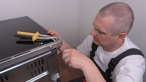 Electrician with screwdriver near electric cooker stock footage