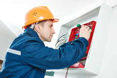 Electrician with screwdriver repair switching electric actuator in fuse box Royalty Free Stock Photography