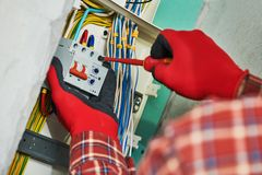 Electrician works with switchbox royalty free stock photo