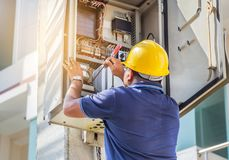 Electrician screwing equipment repairing in fuse circuit breaker box. In residential construction site stock photography