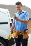 Electrician With Van Sending Text Message On Mobile Phone Outsid Stock Image