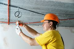 The electrician is setting a bulb. The electrician is setting a light bulb for temporary lighting stock photos