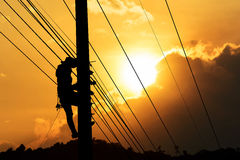 Electrician. Silhouette of electrician working on electric power pole, setting cable wire at sunset background in warm tone Stock Photo