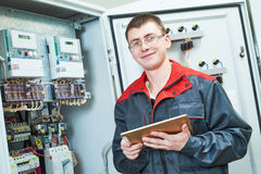 Electrician smiling near switch box with tablet computor Stock Image